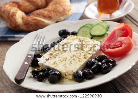 Breakfast with feta cheese, olives, simit, vegetables and tea