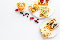 Breakfast with freashly baked belgian waffles on white background top-down frame copy space