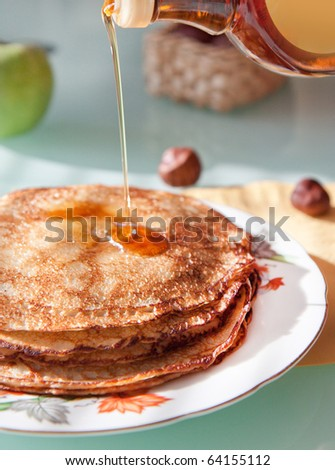 Breakfast with fresh pancakes with syrup and apple