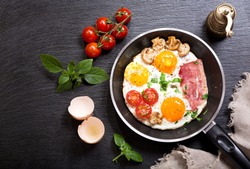 breakfast with fried eggs in a pan with bacon and vegetables on dark background, top view