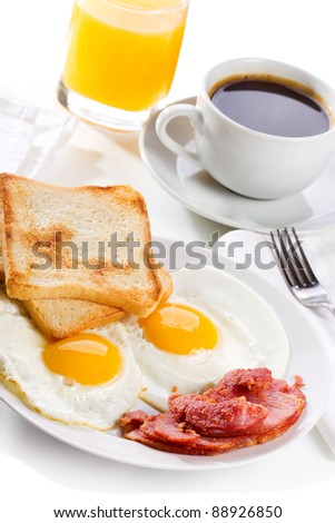 breakfast with  fried eggs, toasts, juice and coffee