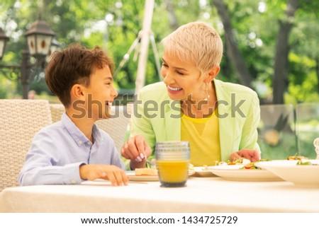 Breakfast with granny. Handsome dark-haired boy feeling happy having breakfast with granny