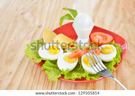 Breakfast with hard boiled eggs, sliced in halves, salad, tomatoes, cheese and bread on the red plate and wooden background