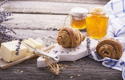 Breakfast with honey butter fresh croissants in the early morning on a simple wooden table in rustic style with blue textiles. The concept is simple natural homemade food. selective Focus
