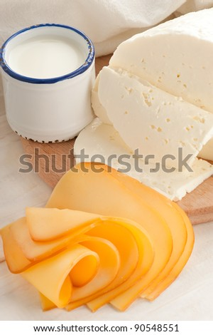 Breakfast with milk and cheese on old wooden table with linen tablecloth
