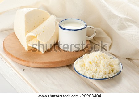 Breakfast with milk, cottage and soft sheep cheese on old wooden table with linen tablecloth