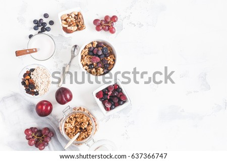 Breakfast with muesli, fruits, yogurt, frozen berries, nuts on white background. Healthy food concept. Flat lay, top view #637366747