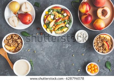 Breakfast with muesli, peach salad, fresh fruit, yogurt on dark background. Healthy food concept. Flat lay, top view #628796078