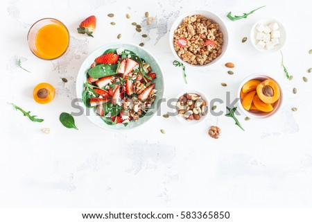 Breakfast with muesli, strawberry salad, fresh fruit, nuts on white background. Healthy food concept. Flat lay, top view #583365850