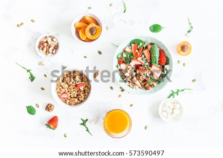 Breakfast with muesli, strawberry salad, fresh fruit, orange juice, nuts on white background. Healthy food concept. Flat lay, top view.