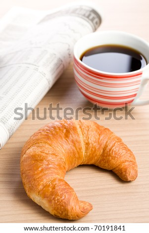 breakfast with newspaper . croissant and coffee