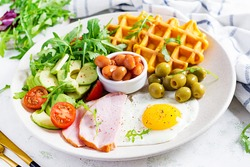 Breakfast with pumpkin waffles, fried egg, ham, tomato, avocado, beans and olives on white background. Appetizers, snack, brunch. Healthy food.