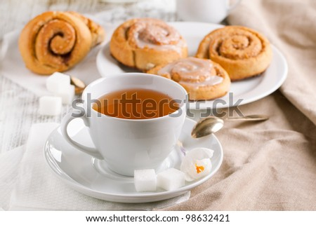 Breakfast with sweet cinnamon buns and cup of tea served on white wooden table - stock photo