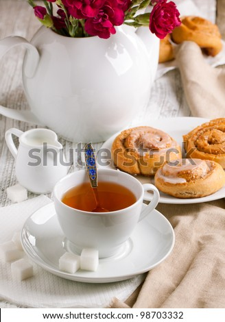 Breakfast with sweet cinnamon buns and cup of tea served on white wooden table