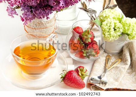 Breakfast with tea and fresh strawberries served on tray with lilac flowers and tableware