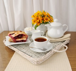 Breakfast with the cherry strudel with tea and milk on a tray