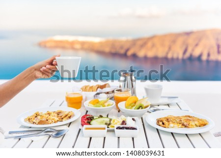 Breakfast woman drinking coffee at luxury hotel resort restaurant table Mediterranean sea view in Santorini, Oia, Greece. Female hand holding coffee cup at morning brunch. Eggs, fruit salad plate. #1408039631
