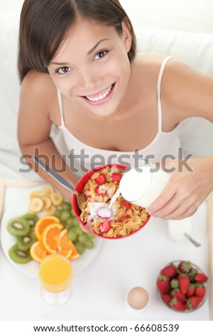 Breakfast woman pouring milk on cereals while eating breakfast in bed. Beautiful smiling young Asian / Caucasian female model.