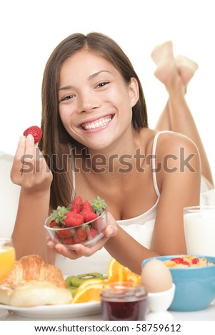 Breakfast. Young woman eating big breakfast in bed showing fresh strawberries smiling. Cute Asian / caucasian model with adorable smile isolated on white background.