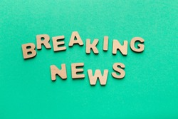 Breaking news phrase spelled with wooden letters on green background. Broadcasting, announcement and urgent information concept, copy space, top view