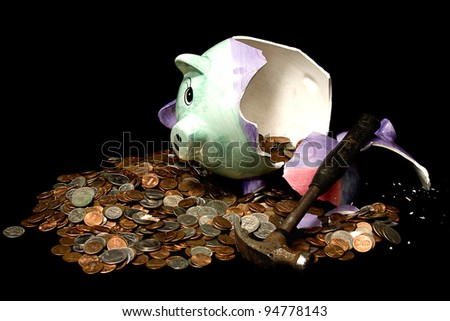 Breaking the bank concept with piggy bank broken by a hammer and all its coins surrounding it
