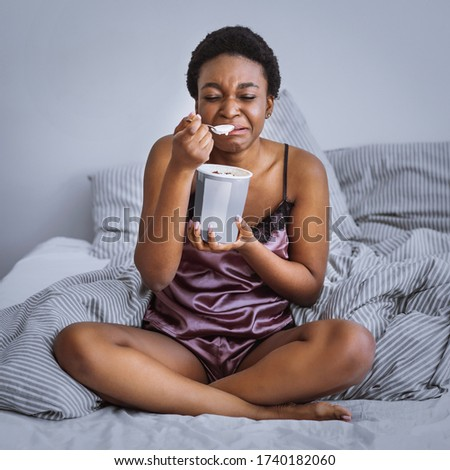 Breakup and sadness concept. Crying african american girl eating ice cream in bed at home Stock photo ©