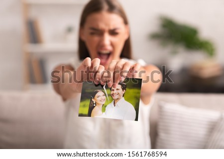 Breakup. Furious Woman Ripping Wedding Photo With Ex-Husband Sitting On Sofa Indoor After Divorce. Selective Focus ストックフォト ©