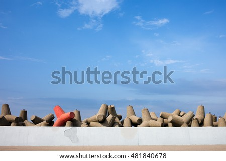 Breakwater protection, solid concrete blocks with one different than others, sea wall embankment ストックフォト ©