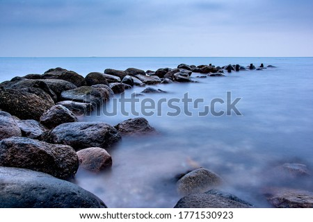 Breakwater Stones in the ocean dark mood for postcards about grief mourning or peaceful and soothing meditation and relaxation Photo stock ©