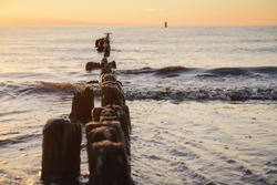 Breakwaters in the Baltic sea over the sunset in summer
