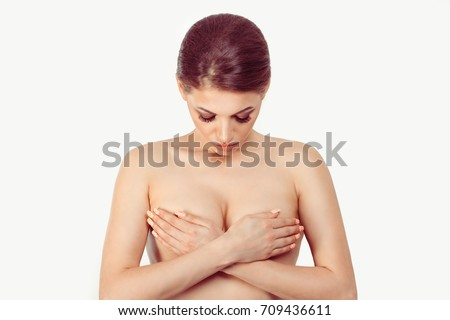 Shutterstock Breast Cancer Awareness, middle age female examining her breast for signs cancer by hands looking down thinking of mammal plastic cosmetic surgery isolated on white grey background wall