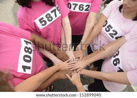 breast cancer awareness race: women in pink  joining hands for support