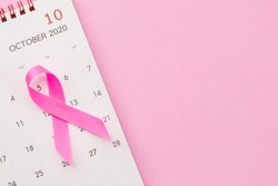 Breast Cancer concept : Top view pink ribbon and calendar symbol of breast cancer campaign on pink background