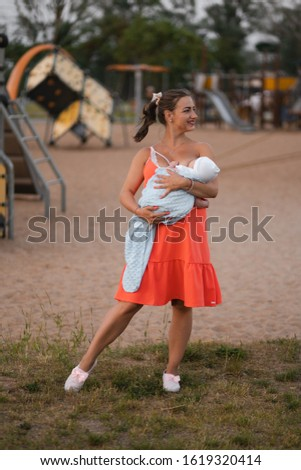 Breast feeding: Young mother breastfeeds her baby boy child in city park standing wearing bright red dress - Son wears white cap - Family values warm color summer scene handheld
