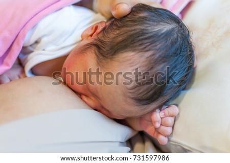 Breastfeeding newborn in hospital.
