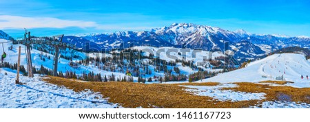 Breath taking scenery of Dachstein West Alps, covered with snow and pine forests, with a view on fast riding chairlift with sportsmen, going to the top of Zwieselalm, Gosau, Salzkammergut, Austria