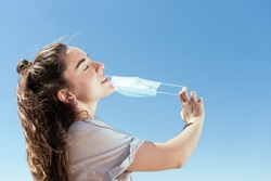 Breathing and feeling free during Coronavirus pandemic concept. Young woman removing a protective surgical mask.