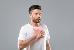 Breathing problem. Sick middle-aged man with chest pain touching inflammated zone and looking at copy space, grey studio background. Bearded man suffering from pneumonia or asthma. COVID-19 concept
