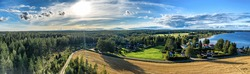 Breathtaking Aerial Panorama on golden ripe rye field, sunny summer field before harvesting. Swedish village at background. Big forest to horizon line, lake, blue summer skies Umea, Northern Sweden