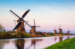 breathtaking beautiful inspirational landscape with windmills in Kinderdijk, Netherlands at sunset. Fascinating places, tourist attraction.