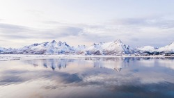 Breathtaking bird's eye view of high mountain rocky peaks covered with white snow reflected in Norway sea water. Breathtaking panoramic fjords landscape of Lofoten in winter, calm beauty of nature