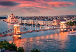 Breathtaking evening view of Parliament and Chain Bridge in Pest city. Amazing spring cityscape of Budapest. Stunning sunset in capital of Hungary, Europe. Traveling concept background.