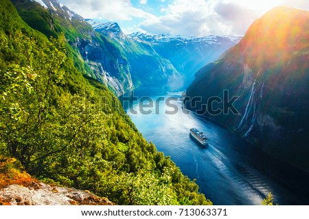 Breathtaking norway view of Sunnylvsfjorden fjord with cruise ship and famous Seven Sisters waterfalls, near Geiranger village in western Norway.