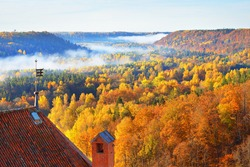 Breathtaking panoramic aerial view of the colorful forest and Turaida castle tower in a morning fog. Fairy autumn landscape. Gauja national park, Sigulda, Latvia