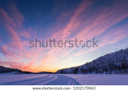 Breathtaking sunset with golden and pink clouds over frozen lake in Lapland.  Pedestrian and snowmobile roads go across snow covered lake. Winter season greeting card background with copy space.