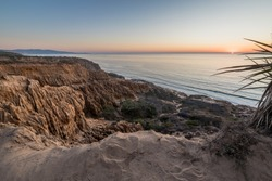 Breathtaking view looking down the rugged sandstone cliffs of Razor Point at sunset, Torrey Pines States National Reserve, La Jolla, California