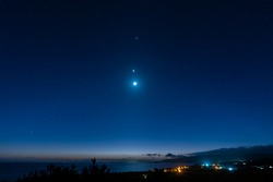 Breathtaking view of a starry sky, Venus, Jupiter and moon line up. Top view of a seashore city before dawn. Iriomote Island, natural world heritage.