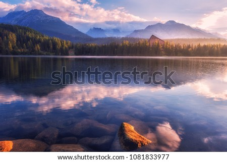 Stock Photo Breathtaking view of the alpine lake and mountains with reflection in the crystal clear water before sunrise. Famous tourist resort lake Strbske Pleso in the High Tatras, Slovakia (Slovensko), Europe