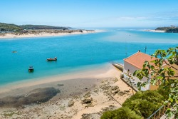 Breathtaking view of the mouth of the River Mira flowing into the Atlantic Ocean - Aquatic lifestyle sport in idyllic turquoise water, Vila Nova de Milfontes, Vicentine Coast Natural Park PORTUGAL
