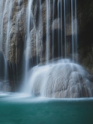Breathtaking view of waterfall smooth flowing stream on limestone cliff, turquoise pond in rainforest. Close up shot. Long exposure. Minimal natural background. Erawan Falls, Kanchanaburi, Thailand.